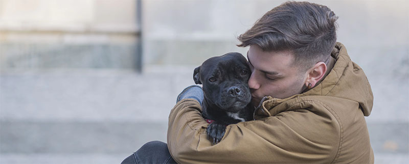 Young man hugs his emotional support dog